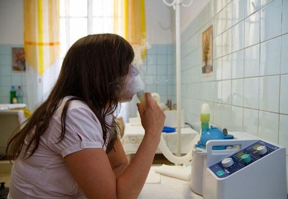 Девушка дышит лекарством из ингалятора