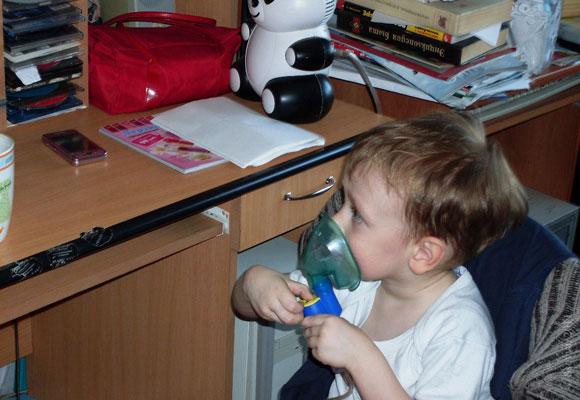 Мальчик лечится дома с помощью ингалятора