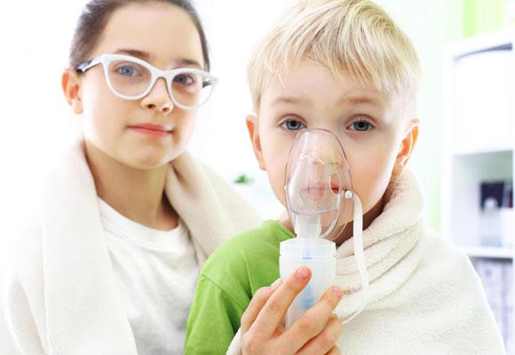 Ребенок при помощи взрослого дышит через ингалятор