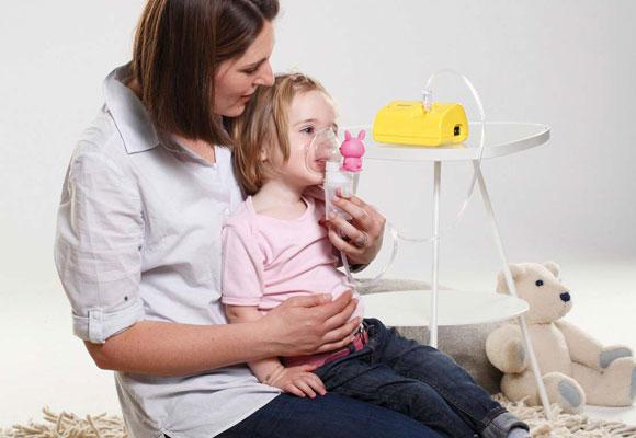 Женщина делает ребенку небулайзерную терапию