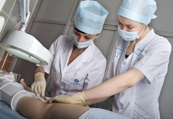 врач вводит углу в вену ноги