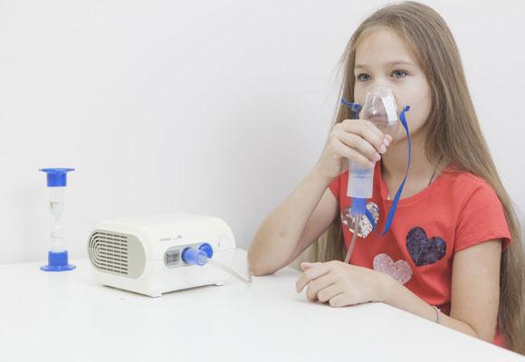 Девочка дышит через маску ингалятора