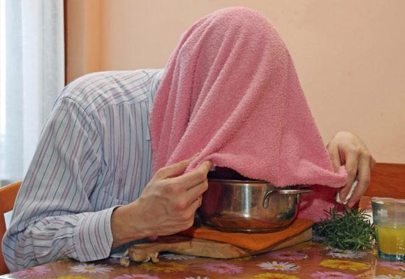 Мужчина, накрывшись полотенцем, делает паровую ингаляцию