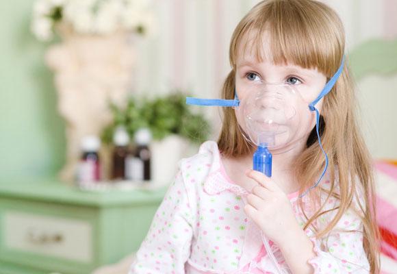 Девочка дышит через ингалятор