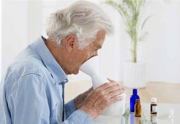 Пожилой мужчина делает паровую ингаляцию