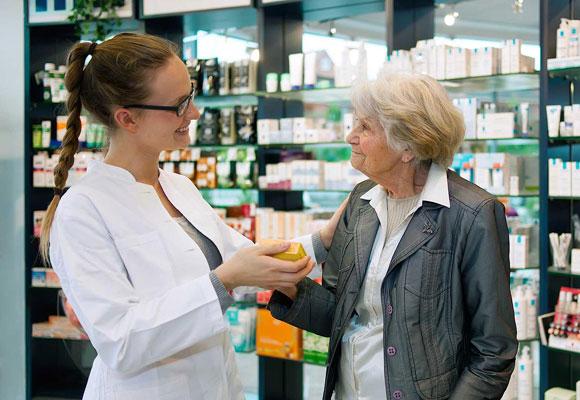 Пенсионерка покупает лекарство в аптеке