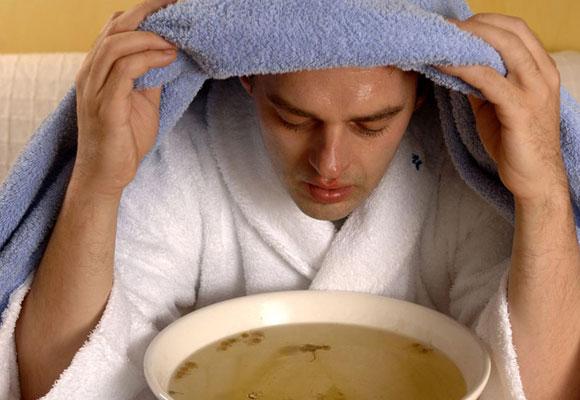 Мужчина с полотенцем на голове делает паровую ингаляцию