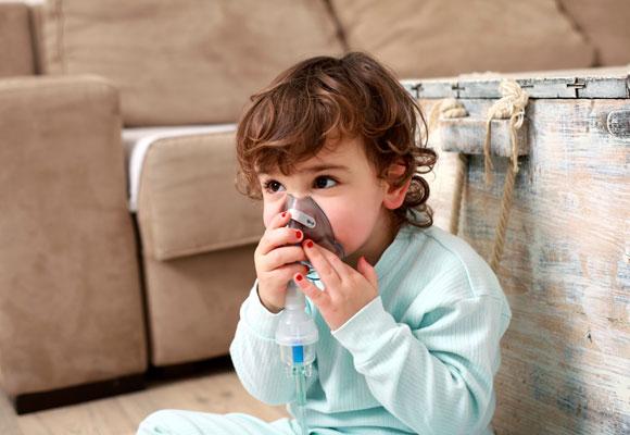 Мальчик держит в руках небулайзерную маску