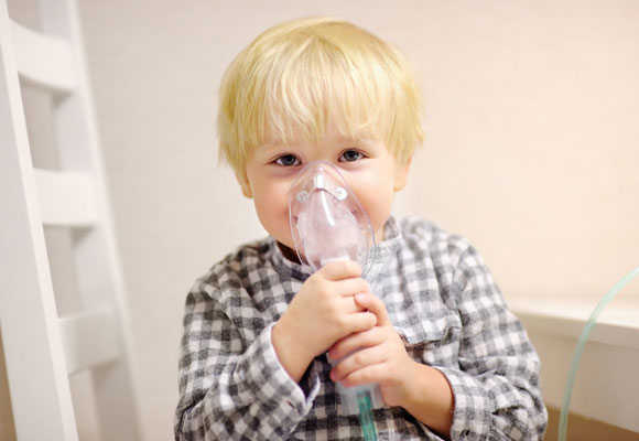 Мальчик дышит через небулайзер