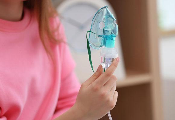 Девушка держит в руке маску небулайзера