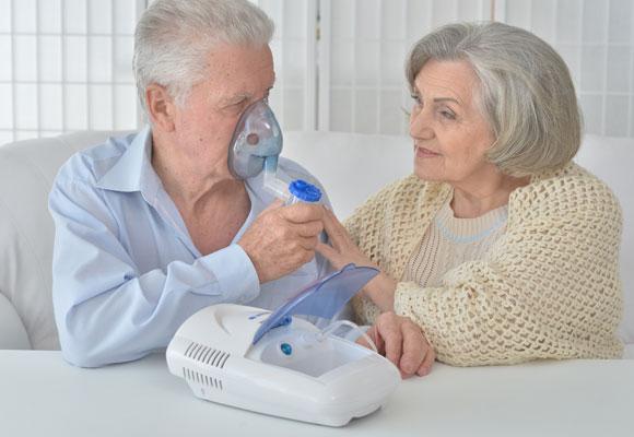 Пожилой мужчина делает себе ингаляцию