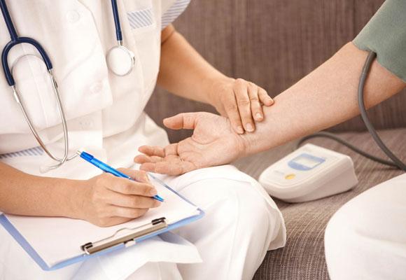 Фармацевт измеряет пульс больного