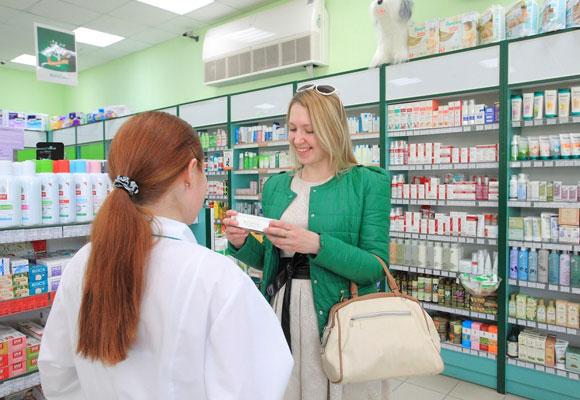 Девушка покупает лекарство в аптеке