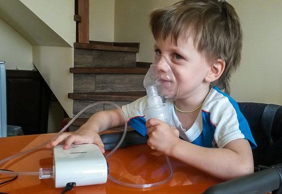 Мальчик пользуется ингалятором в домашних условиях