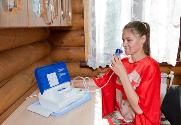 Девушка делает ингаляцию прибором